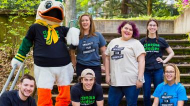 Students with the duck mascot outside sitting on steps