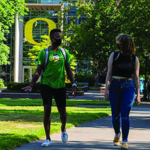 Two people walking on UO campus in front of Lillis Hall