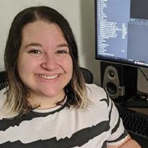 University of Oregon Cinema Studies alum Sabrina Gimenez sitting in front of a computer